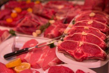 frische Fleischstücke, garniert mit Knoblauch, Kräutern und Zitronenscheiben