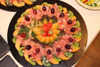 Catering-Teller mit ansprechend angerichteten Fleisch- und Obstwaren